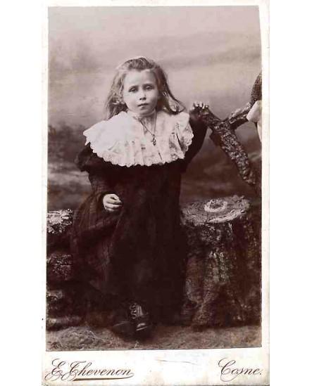 Fillette debout en robe avec grand col de dentelle
