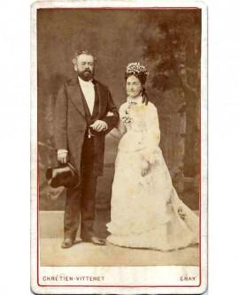 Couple de mariés: homme barbu en habit, chapeau à la main, femme en robe blanche