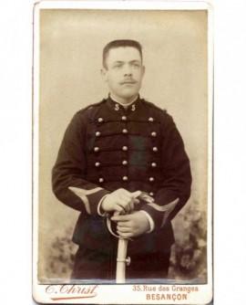 Militaire (caporal) du 5è, tête nue, tenant gants et sabre