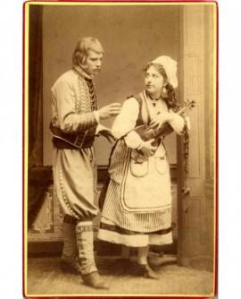 Couple en costume régional, la femme retenant un violon