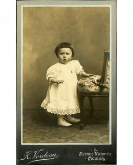 Petit enfant en robe, appuyé sur un fauteuil