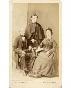 Vieux couple assis, un prêtre (leur fils?) debout entre eux