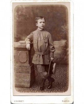 Jeune garçon au sarrau boutonné, ceinturon, canotier à la main