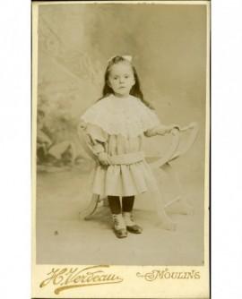 Petite fille en pied, accoudée à un fauteuil