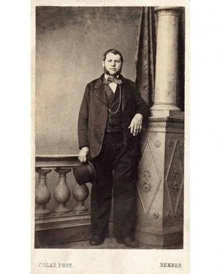 Homme barbu, debout contre une colonne, son chapeau à la main
