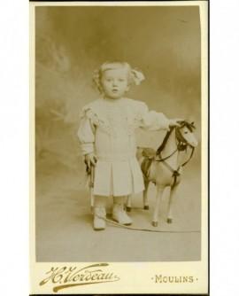 Petite fille en robe, avec fouet et cheval ( jouet)