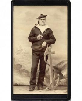 Marin en uniforme, appuyé sur une ancre factice (militaire)