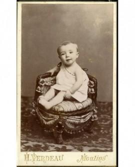 Bébé en chemise, souriant, assis sur un fauteuil