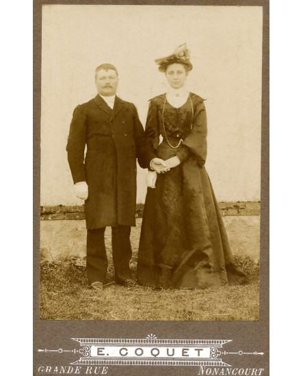 Couple endimanché se donnant la main, posant dans un champ