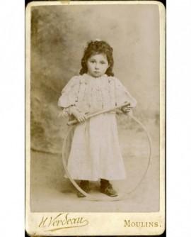 Petite fille en robe de dentelle avec baguette et cerceau (jouet)