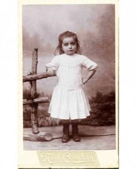 Fillette en robe blanche, appuyée sur barrière factice