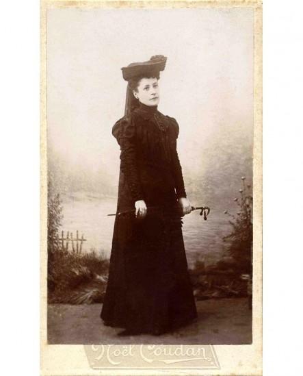 Femme en chapeau et manteau noir, tenant une ombrelle devant elle