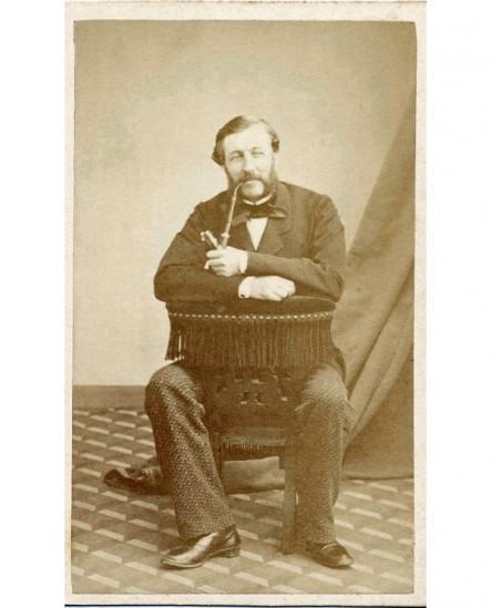 Homme barbu, assis à califourchon, pipe au bec