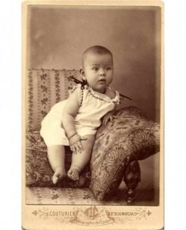 Bébé en chemise et pieds nus assis dans un fauteuil