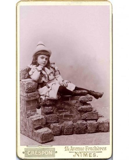 Fillette au chapeau pointu, assise sur des pierres