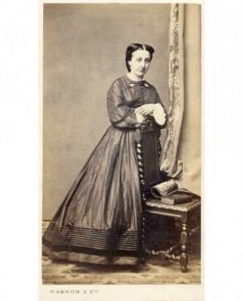 Femme en robe appuyée sur une chaise (livre)