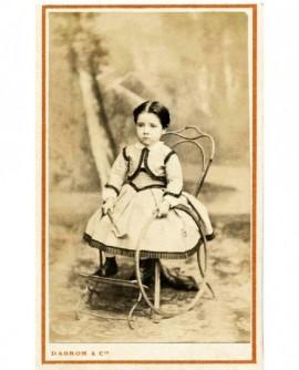Fillette en robe, chaise de jardin, cerceau. jouet