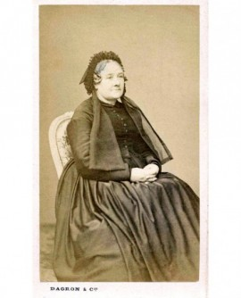Femme en robe et bonnet à rubans assise, mains jointes