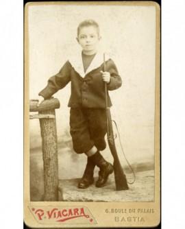 Petit garçon corse en col marin debout, un fusil de bois à la main