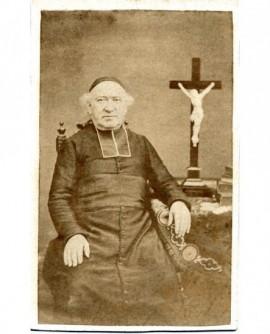 Ecclésiastique en calotte assis, un crucifix près de lui