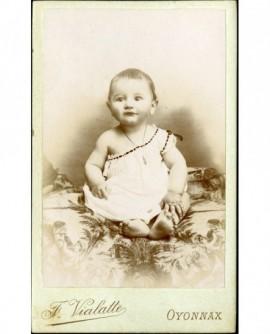 Bébé en chemise, épaule dénudée, assis sur une tenture