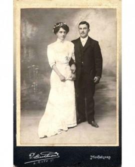 Couple de mariés se donnant le bras (la femme tient son éventail)