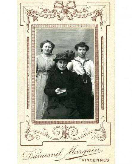 Trois femmes, la plus âgée devant en chapeau, livre à la main