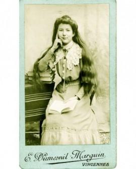 Jeune fille à longs cheveux, accoudée sur des livres (de prix?)