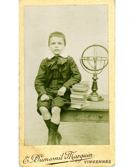 Garçon assis accoudé sur une pile de livres près d'une sphère armillaire
