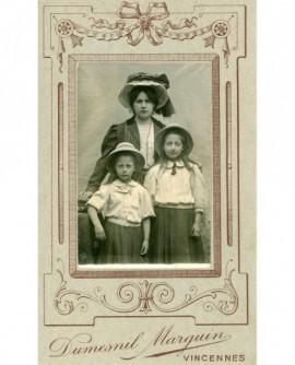 Femme en chapeau avec ses deux filles en corsage-jupe etchapeau