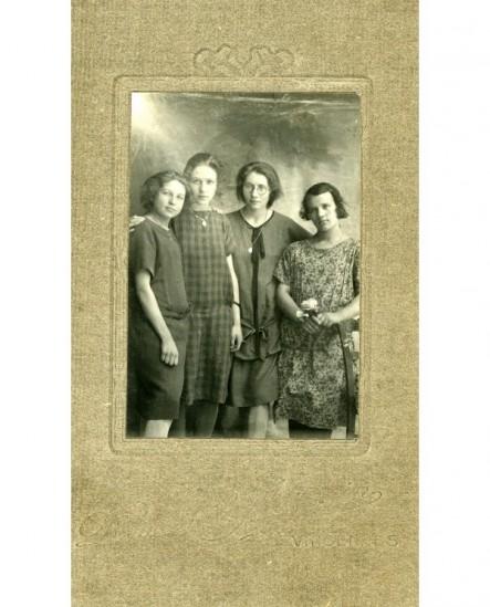 Groupe de quatre jeunes filles (celle de gauche tient une fleur)
