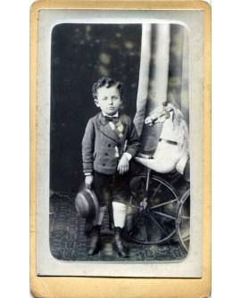 Jeune garçon posant avec une médaille de meilleur élève à côté d'un cheval de bois. jouet