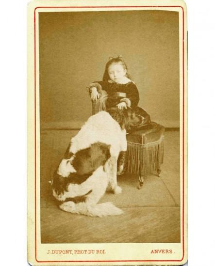 Fillette assise caressant un gros saint-bernard