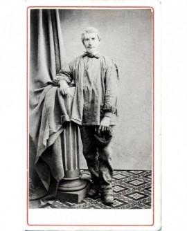 Homme en blouse debout appuyé à une colonne