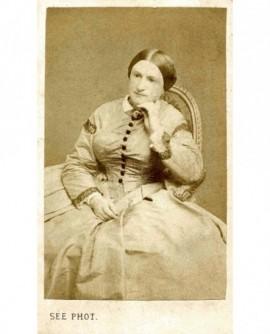 Femme en robe assise, se tenant la tête