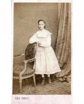 Fillette debout en robe blanche appuyée à une chaise
