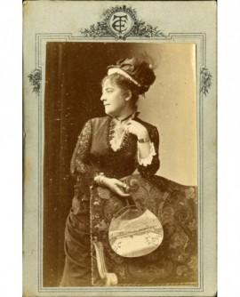 Femme en chapeau, de profil, avec éventail ouvert
