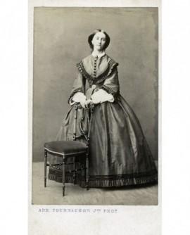 Femme en robe debout appuyée sur une chaise