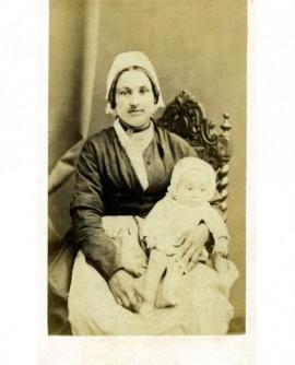 Nourrice en coiffe tenant un bébé sur ses genoux