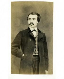 Homme moustachu debout, main dans sa poche de veste