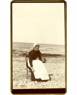 Femme en coiffe assise au bord de la mer (sablaise?)