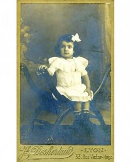 Fillette en robe blanche assise dans un fauteuil curule