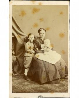 Femme assise, bébé sur ses genoux, garçon debout