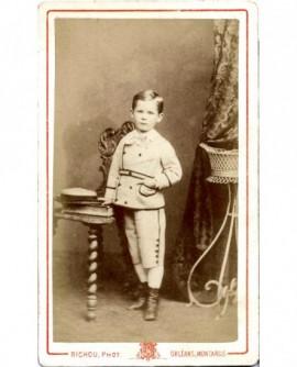 Petit garçon debout, main dans sa poche, son chapeau posé sur une chaise