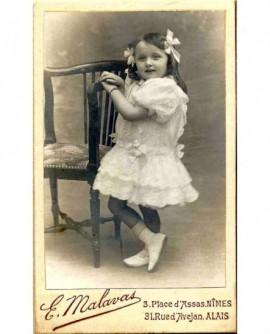 Fillette debout en robe blanche, appuyée à une chaise