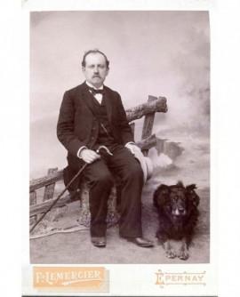 Homme moustachu assis,tenant canne et chapeau à la main, un chien à ses pieds