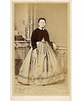 Jeune femme debout, accoudée à une balustrade