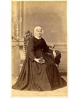 Femme en coiffe assise, accoudée à une table, un livre à la main