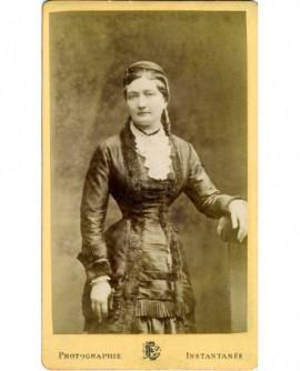 Femme en robe debout, accoudé à une chaise