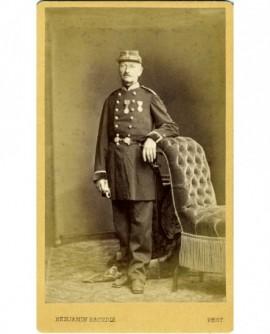 Militaire (officier général) décoré debout, accoudé à un fauteuil, ses gants à la mai
